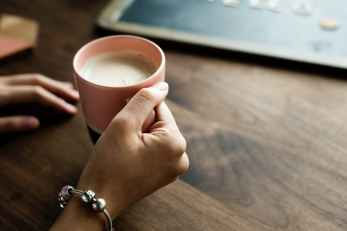 person holding pink ceramic mug